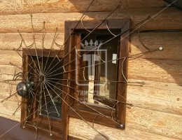 Кованый паук на оконной решетке и решетки на половину окна с подставками для цветов